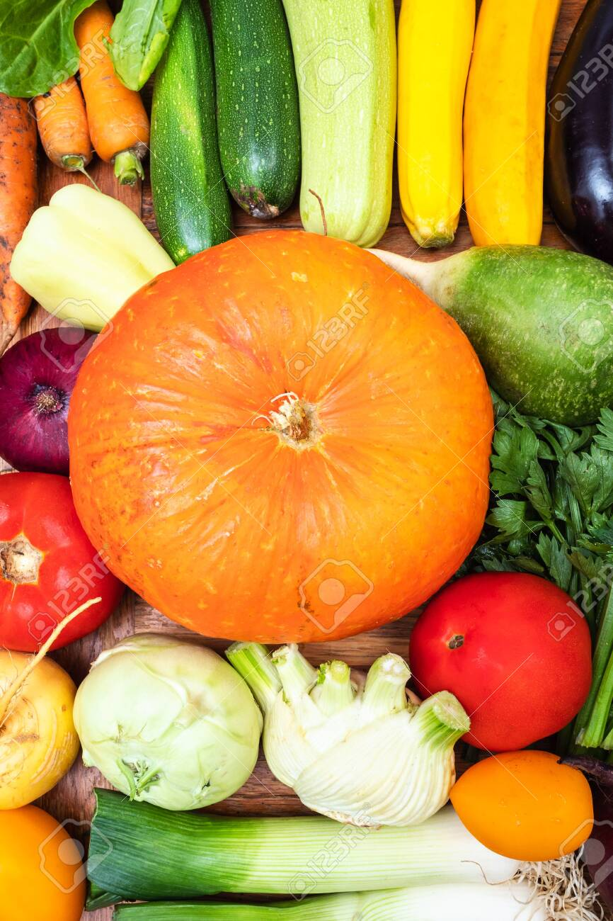 food vertical background - top view of fresh vegetables on wooden table - 129018842