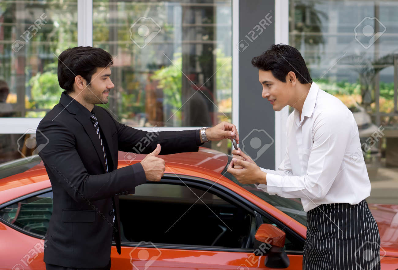 A Persian businessman in a black suit smiles and thumbs up while handling sport car key to the valet service staff. - 165484537