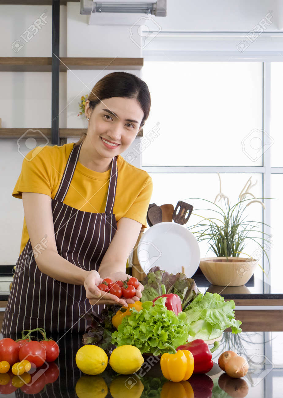 Young asian housewife holding red tomatoes with both hands. The Basket full of various kinds of vegetables. Morning atmosphere in a modern kitchen. - 167016342