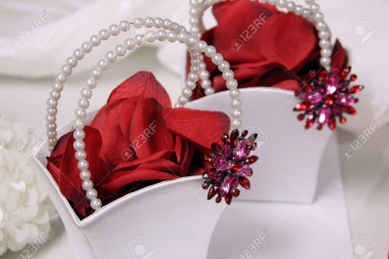 Banque dimages , fleur blanche de filles avec des paniers remplis de perles poignées rouge et décoré de pétales de fleurs de rose et rouge Broches
