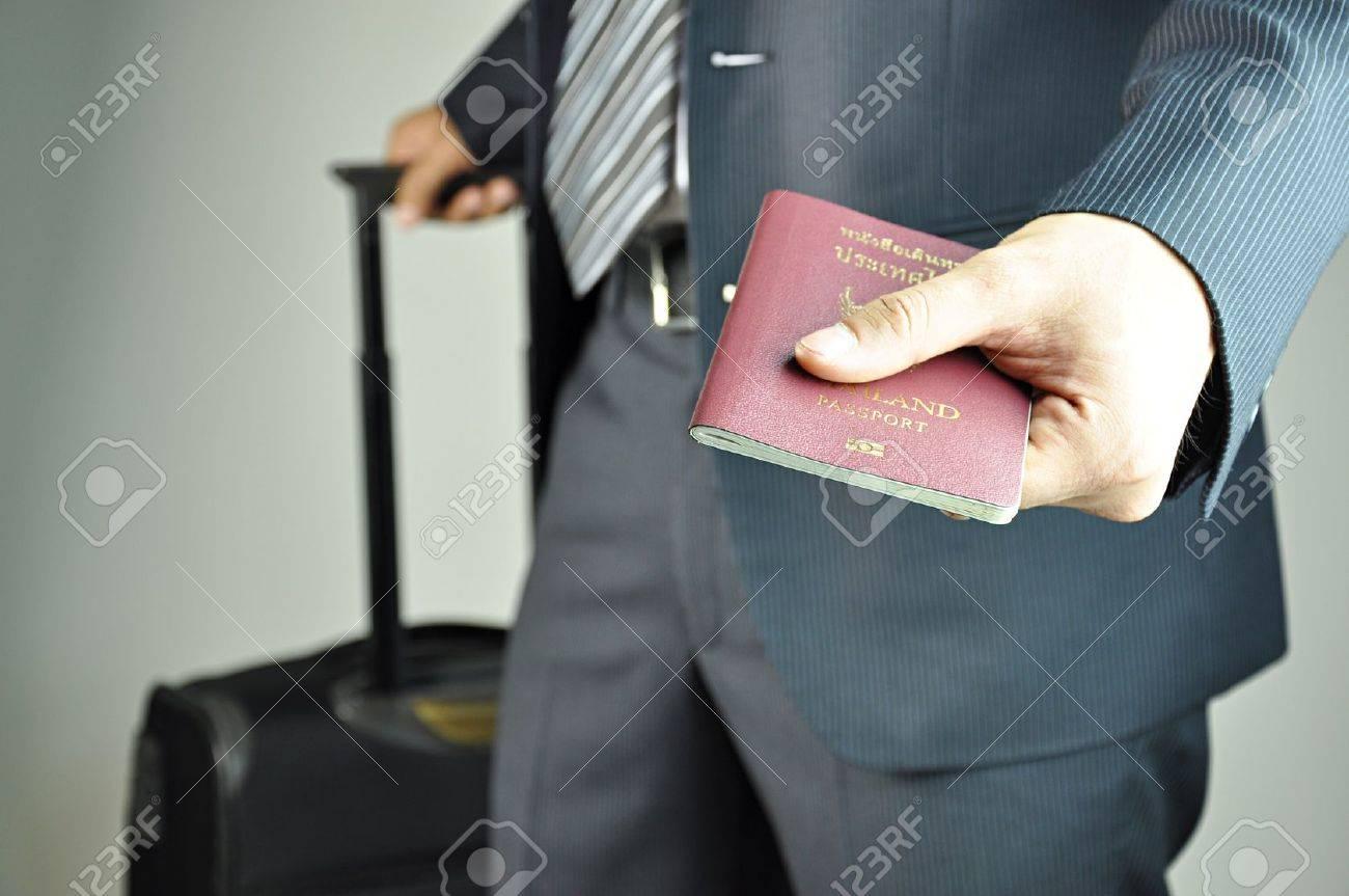 Traveling businessman handing passport Stock Photo - 16849786