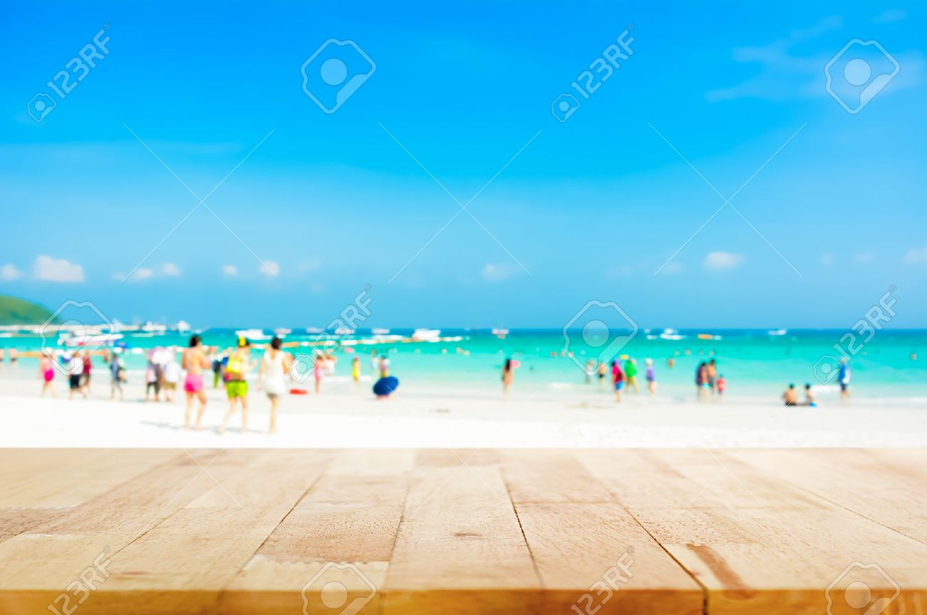 Background image beach - Wood Table Top On Blurred Beach Background With People In Colorful Clothes Can Be Used