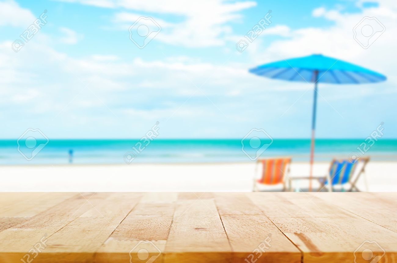 Wood Table Top On Blur Beach Background With Beach Chairs And