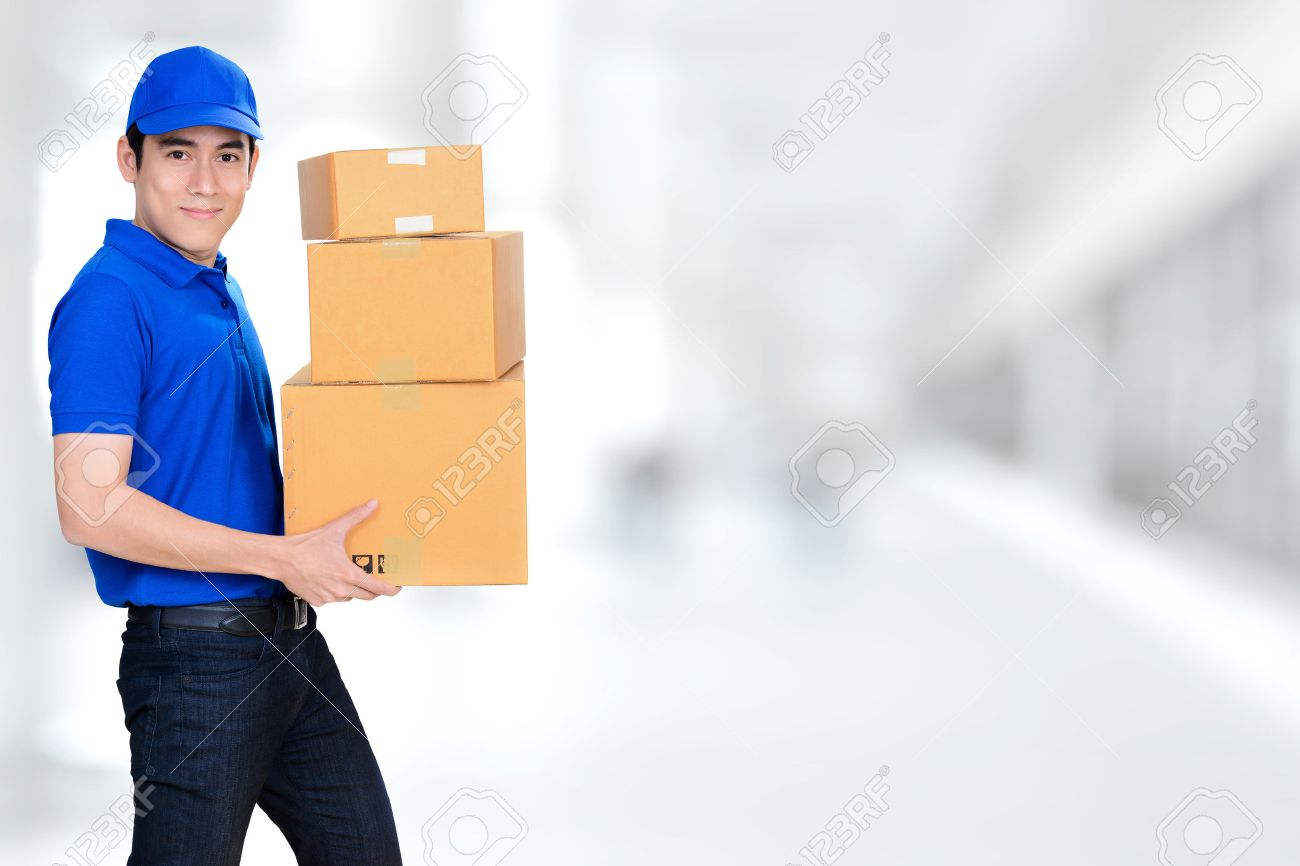 smiling friendly delivery man carrying parcel boxes on blur white