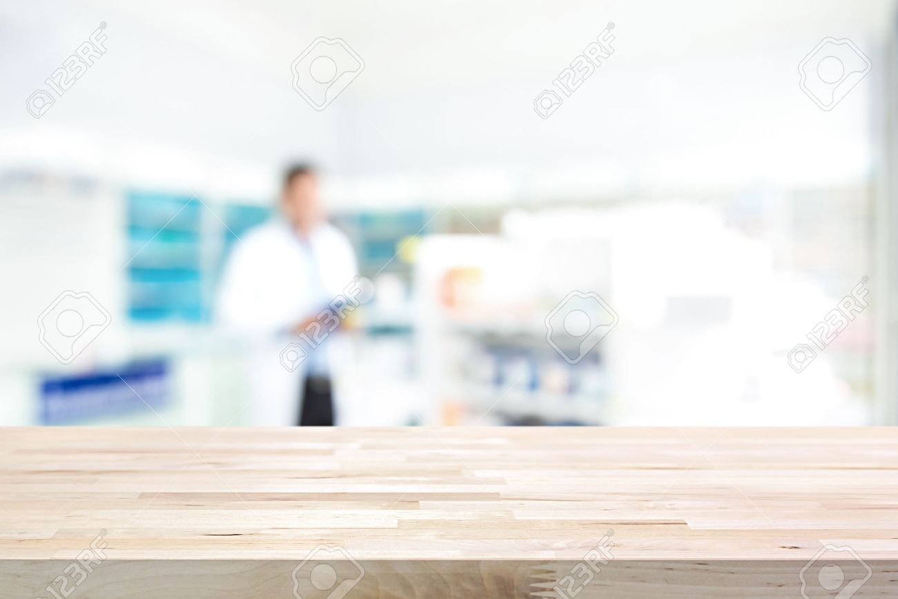 Empty wood counter top on blur pharmacy (chemist shop or drugstore) background - 65690318