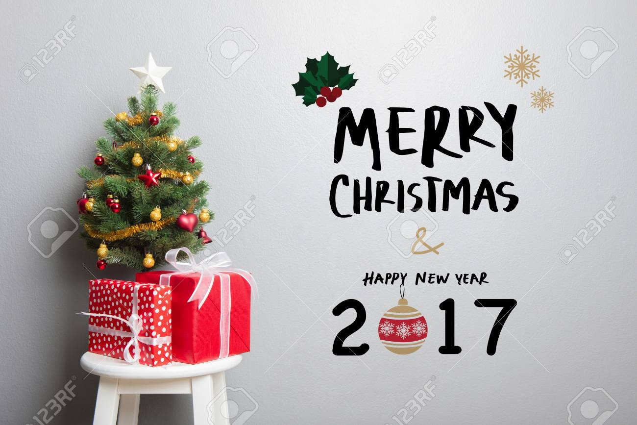 gift boxes and small decorated christmas tree on the chair with merry christmas and happy new