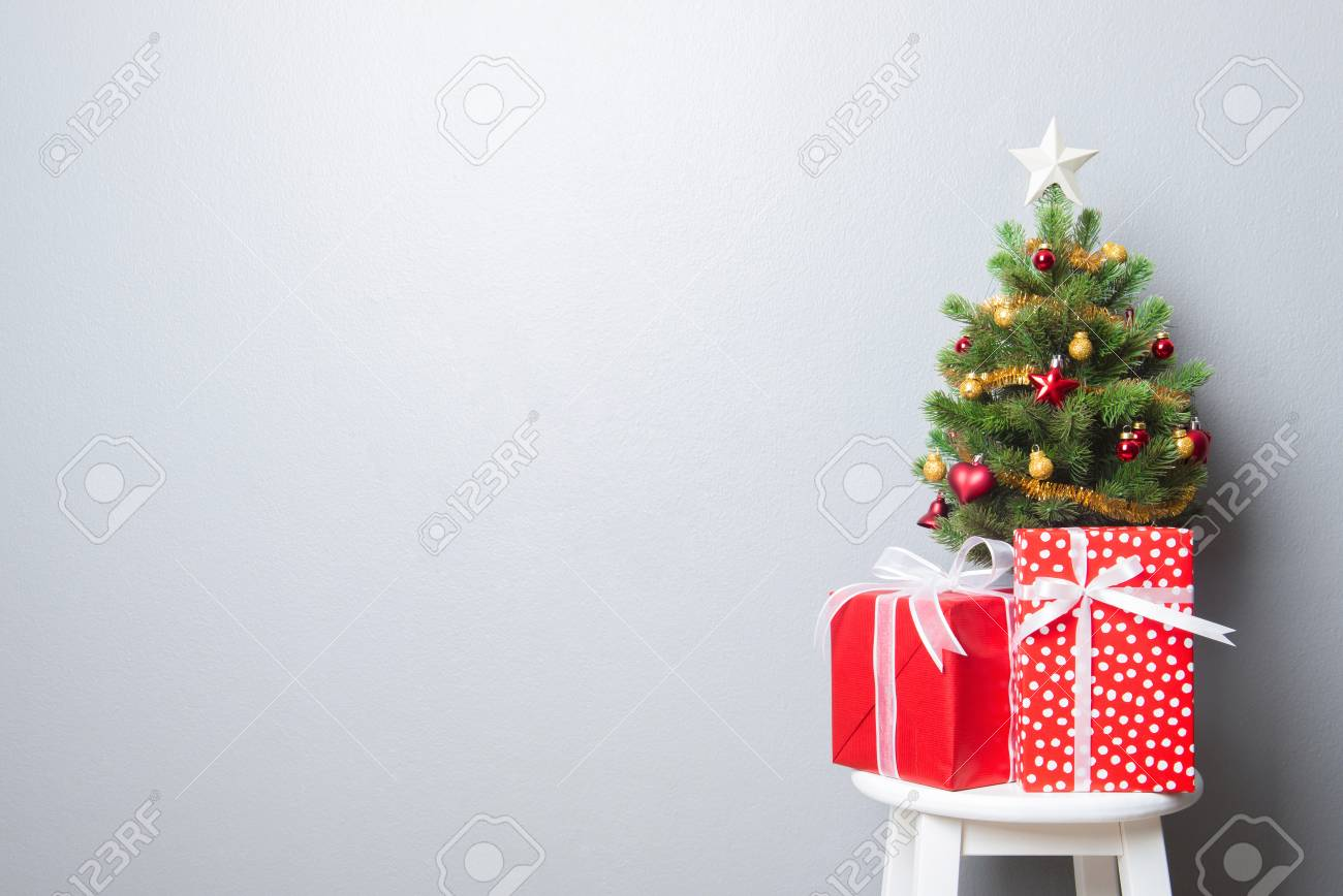 gift boxes and small decorated christmas tree on gray wall background stock photo 66465133