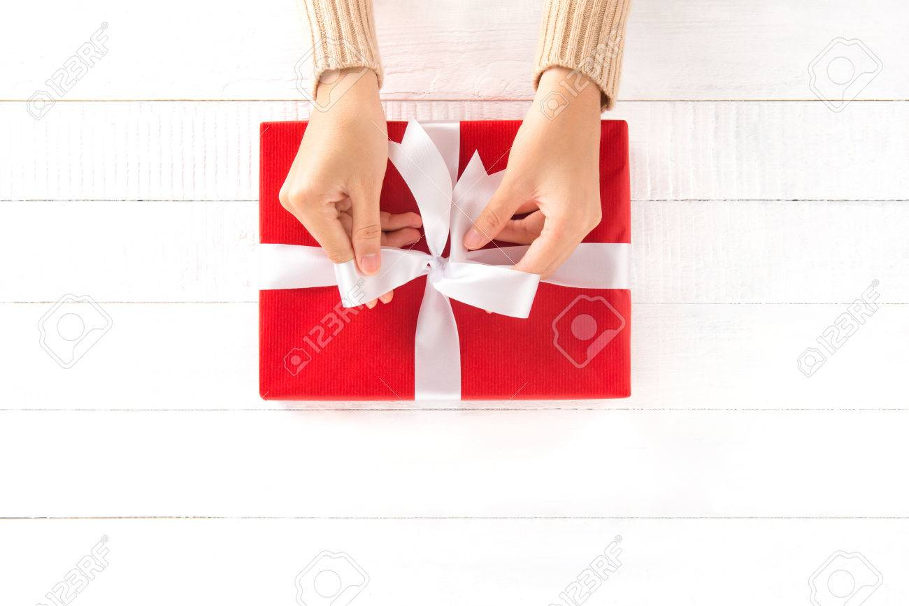 Uncategorized Tying Ribbon hands tying ribbon on red gift box top view stock photo picture 70291696