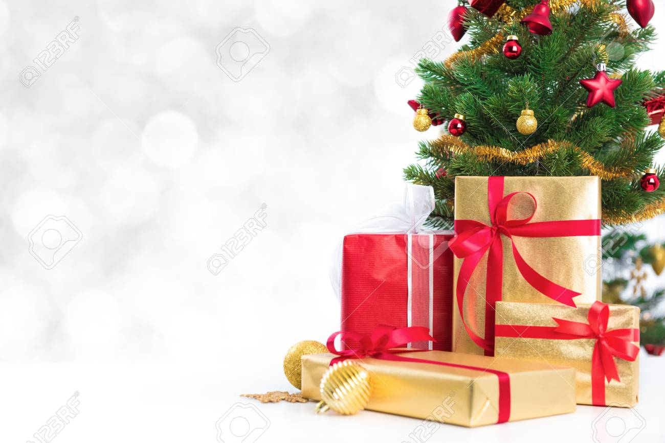 gift boxes and colorful decorated christmas tree on white bokeh background stock photo 70291749