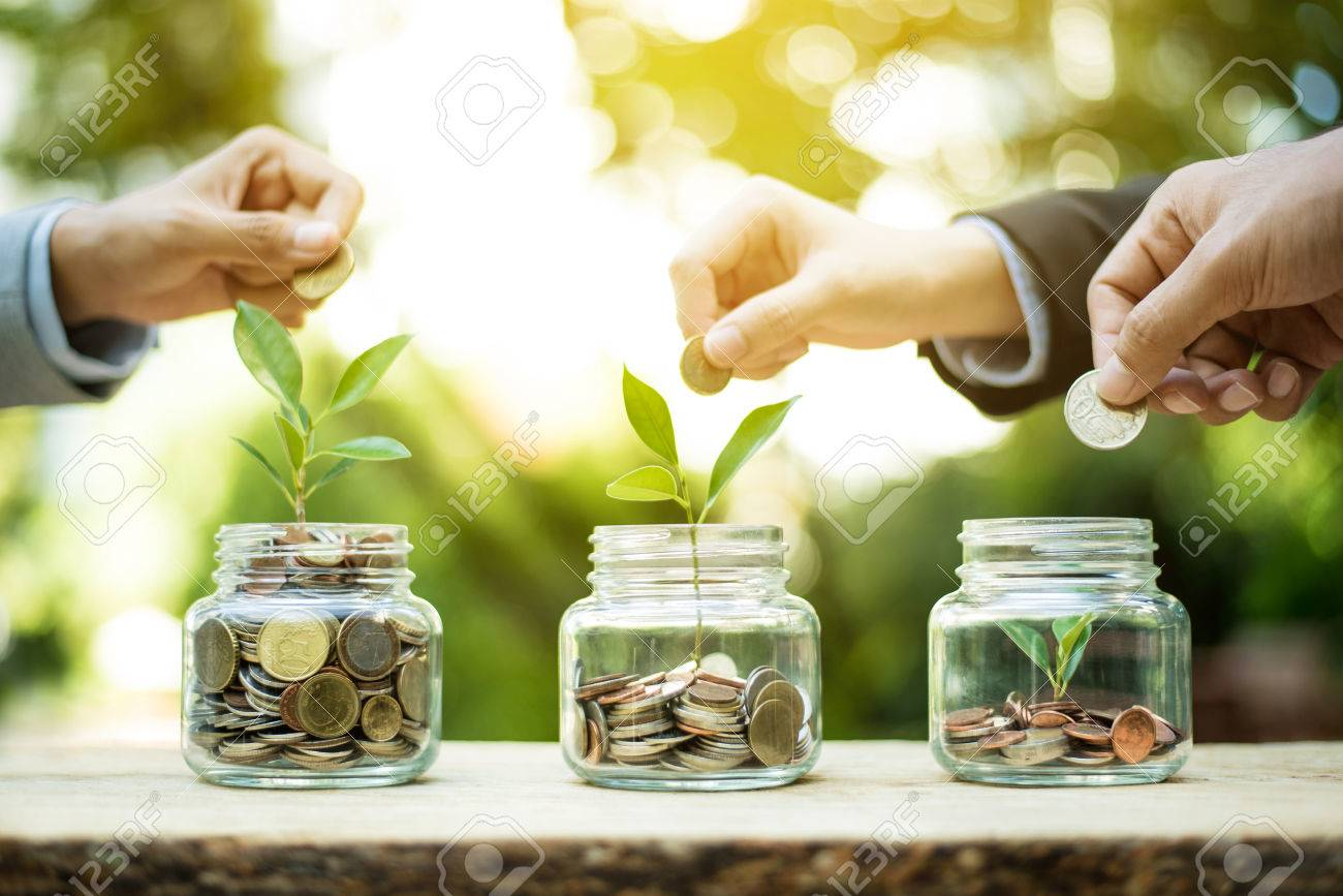 Businessman hands putting money (coin) into the glass jar - savings and investment concept - 71246170