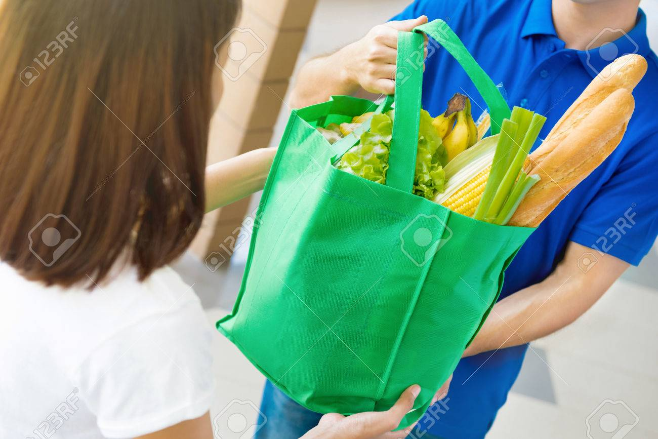 Delivery man giving grocery bag to a woman - food shopping service