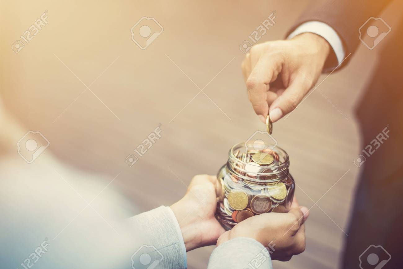 Businessman hand putting money (coin) in the glass jar held by a woman, vintage tone effect - 81597669