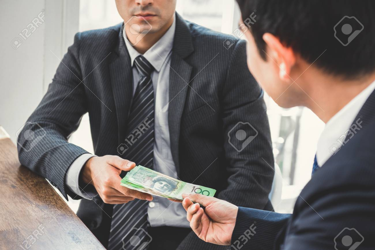 Businessman giving money, Australian dollars, to his partner - bribery and corruption concepts - 90376107