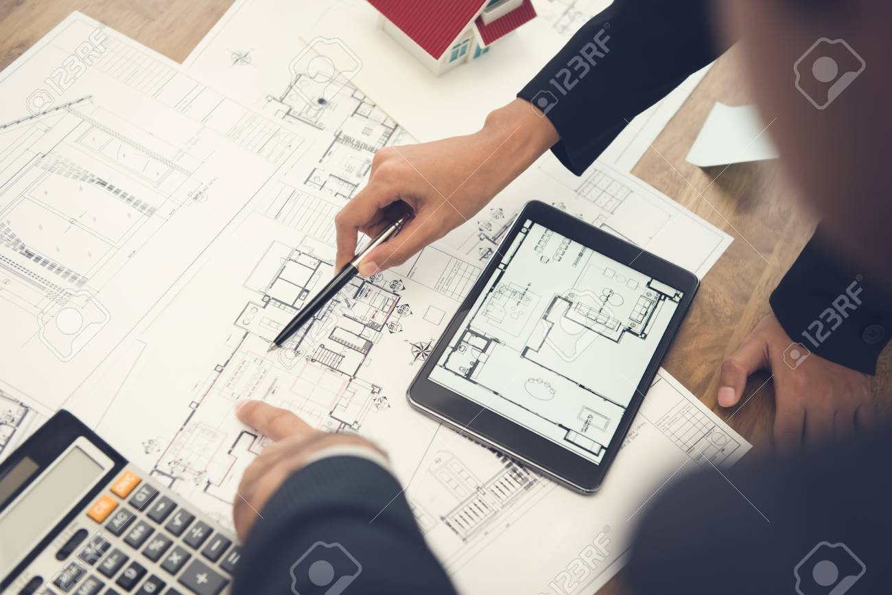 Architects or interior designers discussing floor plan blueprints on the table - 89965883