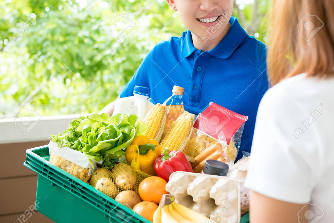 Grocery store delivery man wearing a blue polo-shirt delivering
