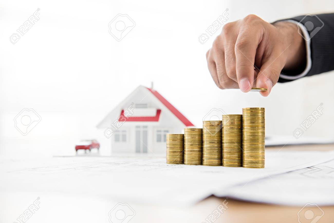 Businessman Putting Coin On Top Of Growing Stacks, Saving Money For Buying  House Or Investing