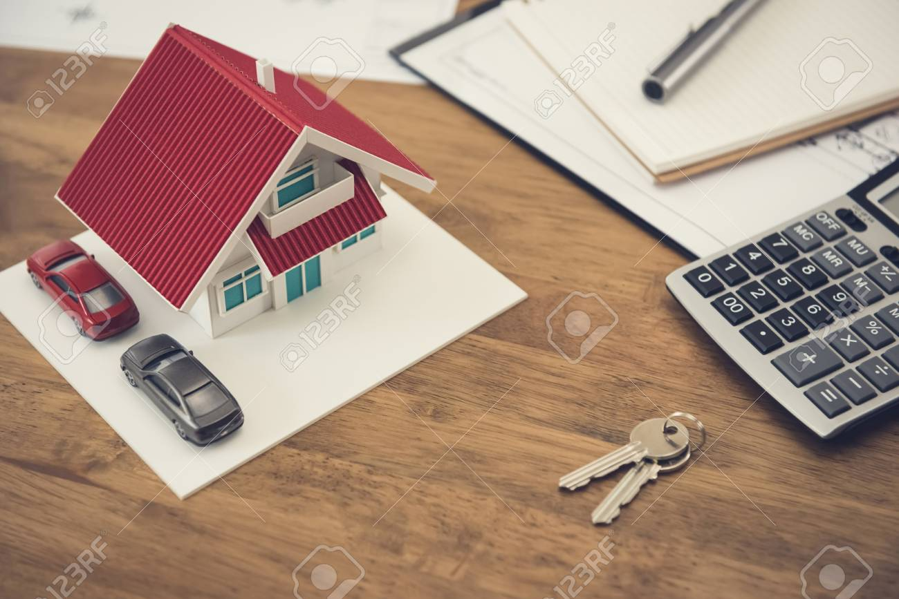 House model, key and calculator with documents on the table - real estate and property concept - 92770271