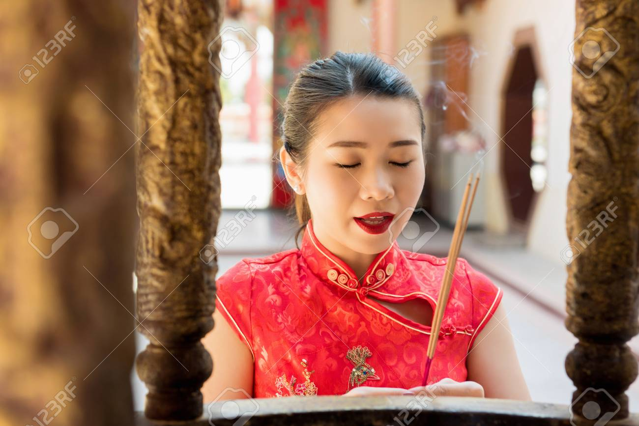 b1245e239 Asian woman in traditional red qipao dress praying with incense sticks  during Chinese or Lunar new