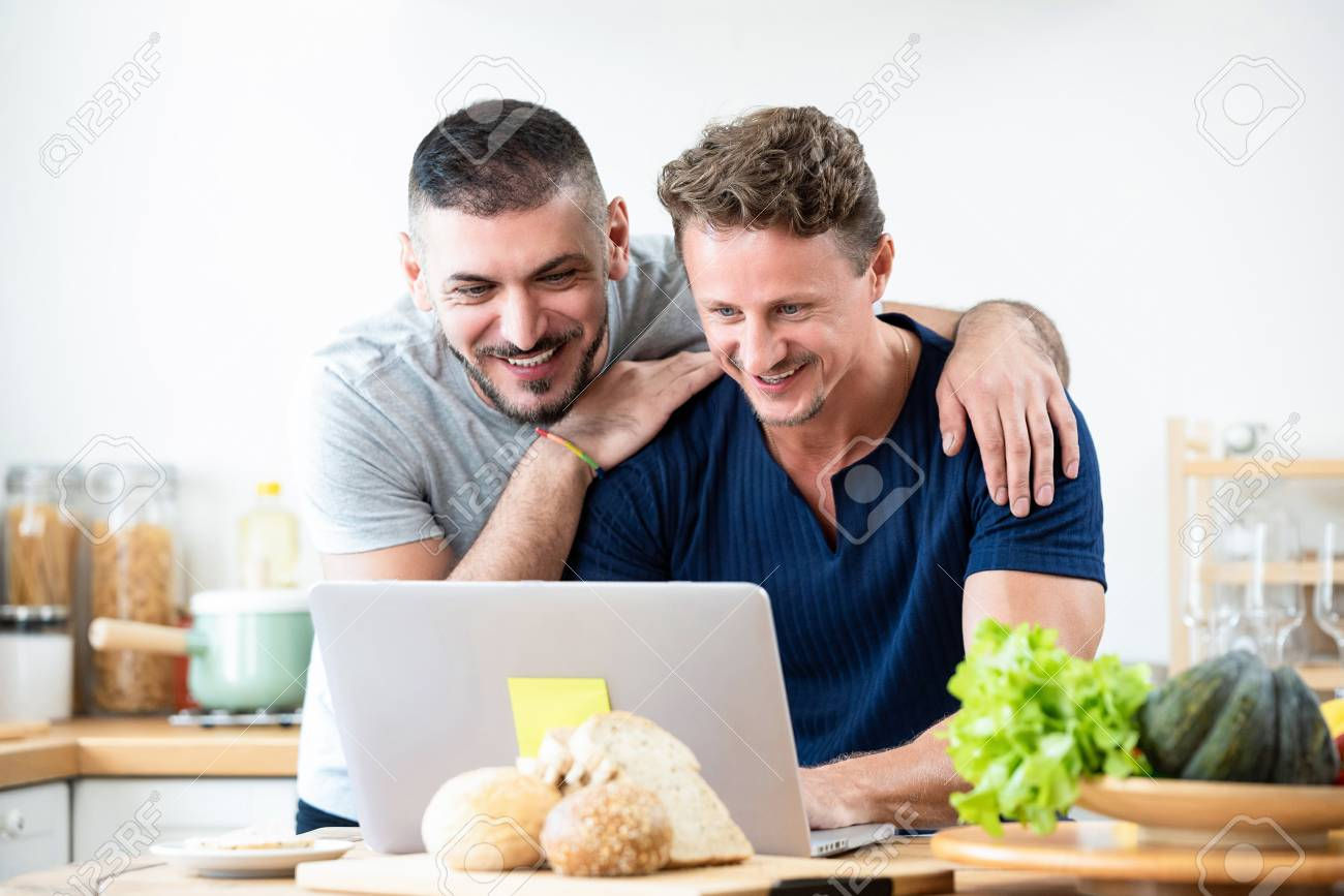 f183528ecc Happy gay male couple browsing internet having a good time together in  kitchen at home Stock