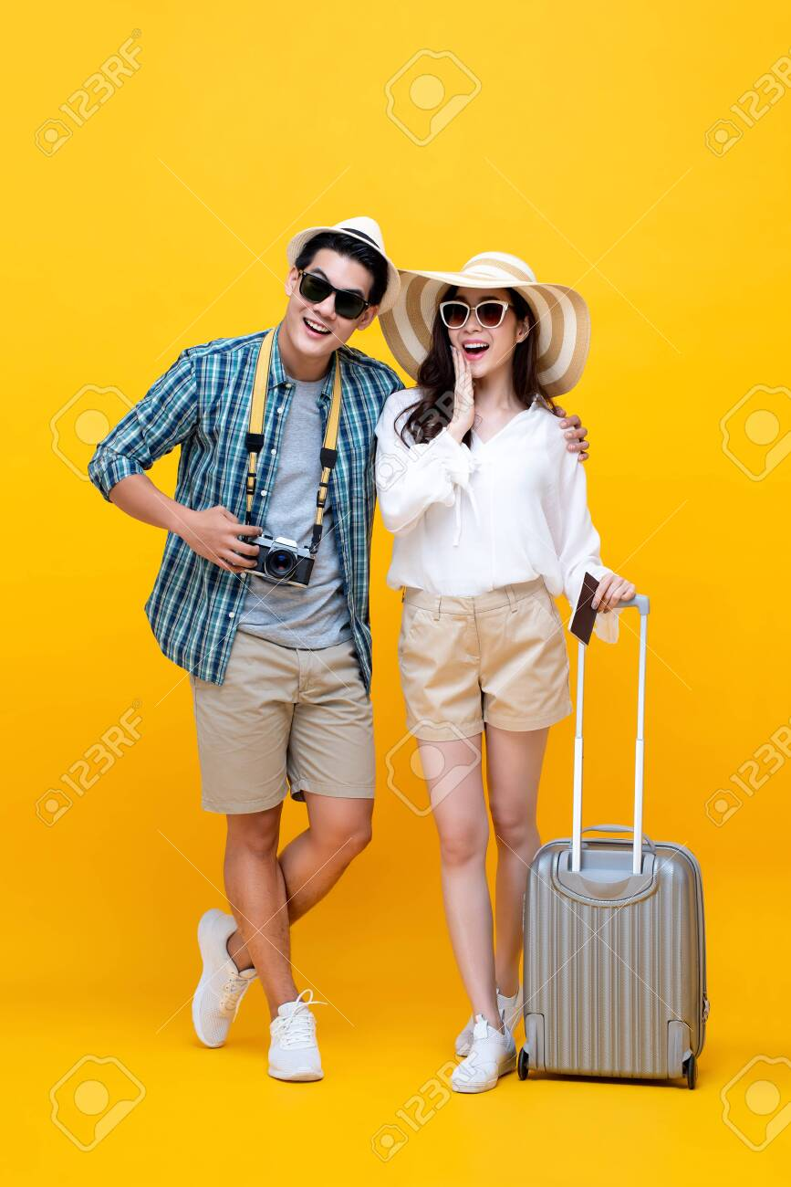 Happy excited young Asian couple tourists in colorful yellow background - 128521080