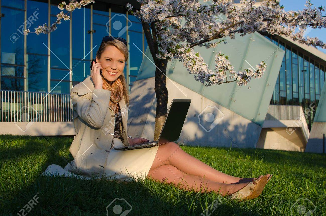 Young pretty woman with laptop talking mobile phone - 21735141