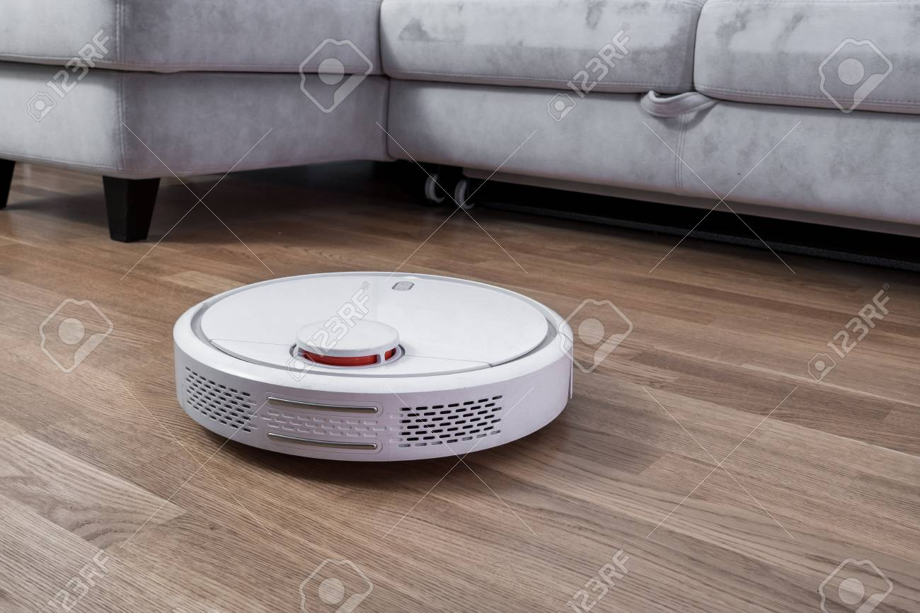 Robotic vacuum cleaner runs near sofa in room on laminate floor. Robot controlled by voice commands to direct cleaning. Modern smart cleaning technology housekeeping. - 123348662