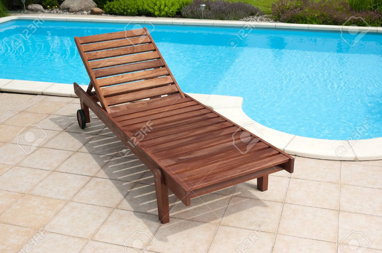 Wooden garden deckchair standing by the pool Stock Photo - 24478140