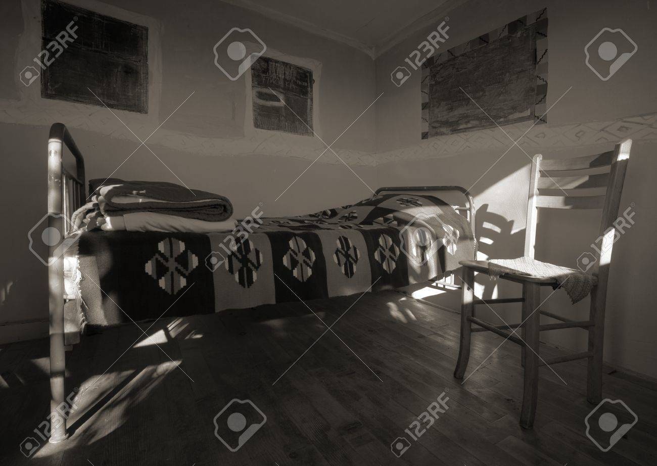 Old wooden house interior, empty room with bed and chair. Stock Photo - 8858551