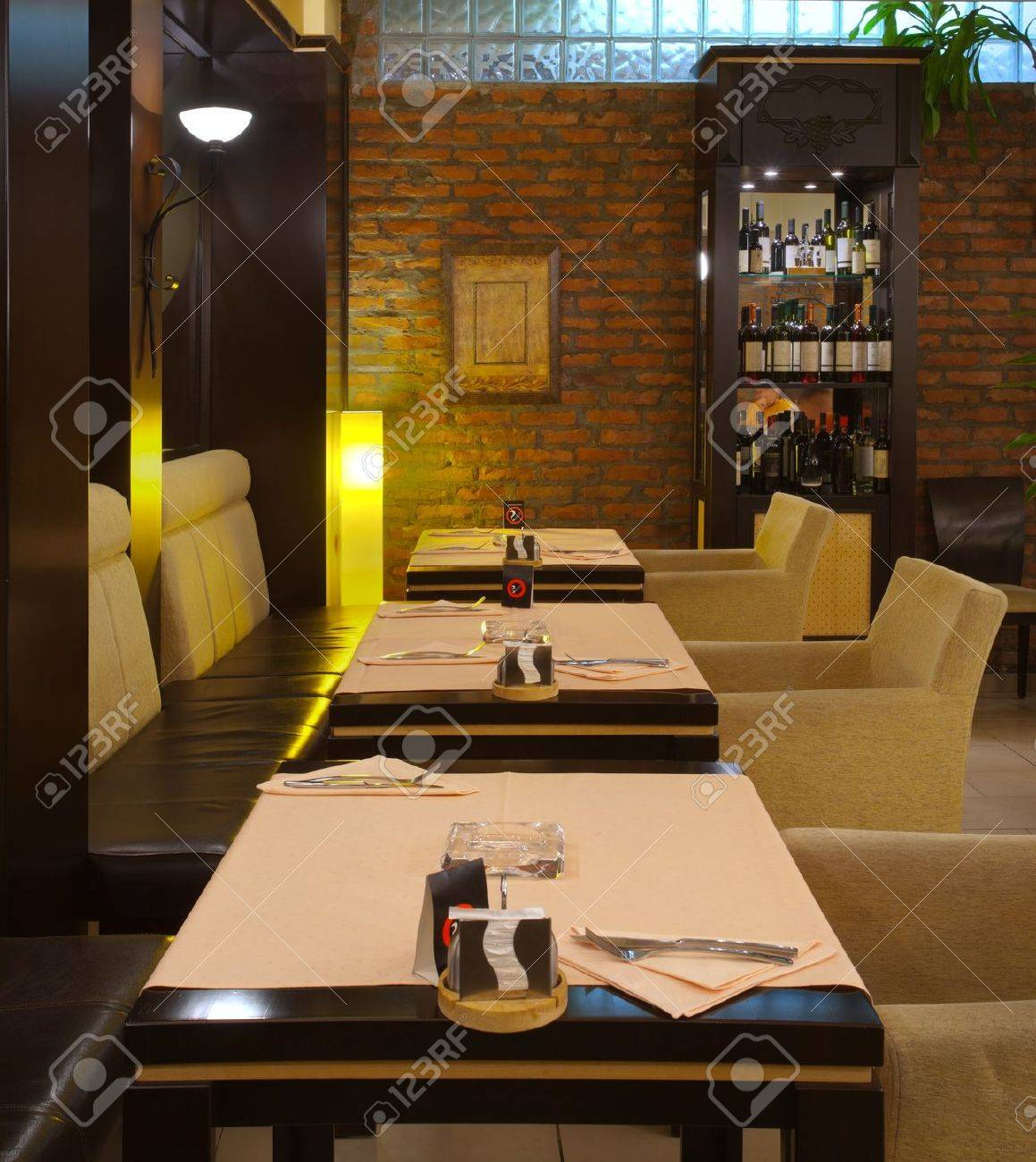 Tables, chairs, brick wall and lighting equipment of a restaurant. Stock Photo - 9009626