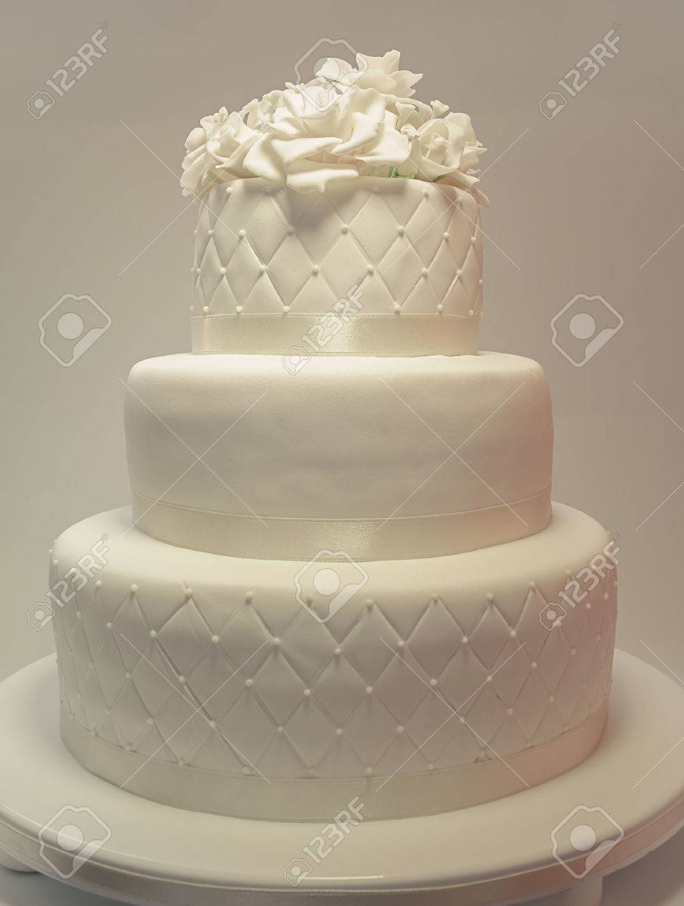 Details Of A Wedding Cake Decoration With White Fondant On White