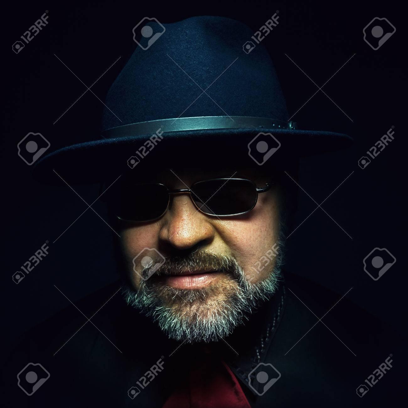online qui aspetto estetico nuovo prodotto Barba uomo di mezza età che indossa cappello nero e occhiali da sole.