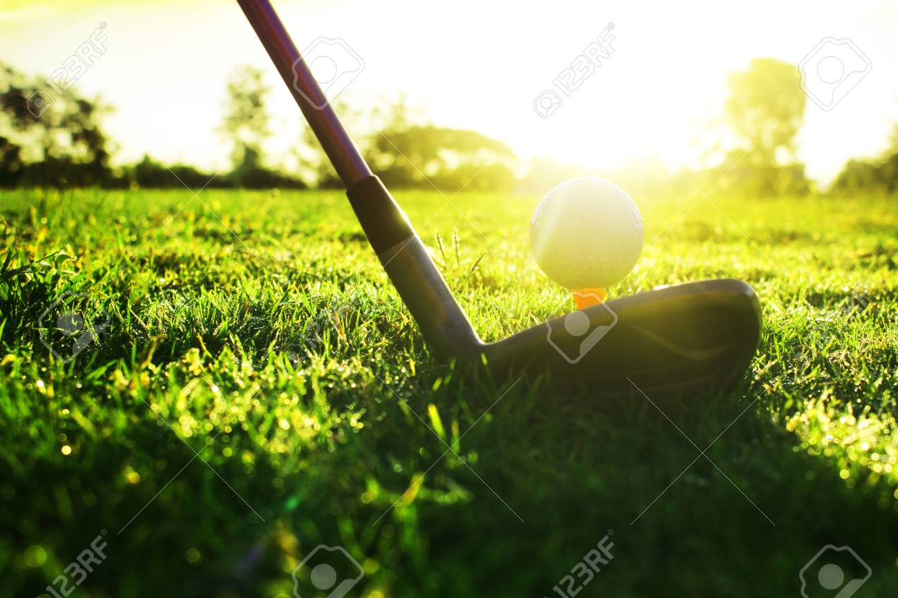 Golf clubs and golf balls on a green lawn in a beautiful golf course with morning sunshine.Ready for golf in the first short.Sports that people around the world play during the holidays for health. - 120025753
