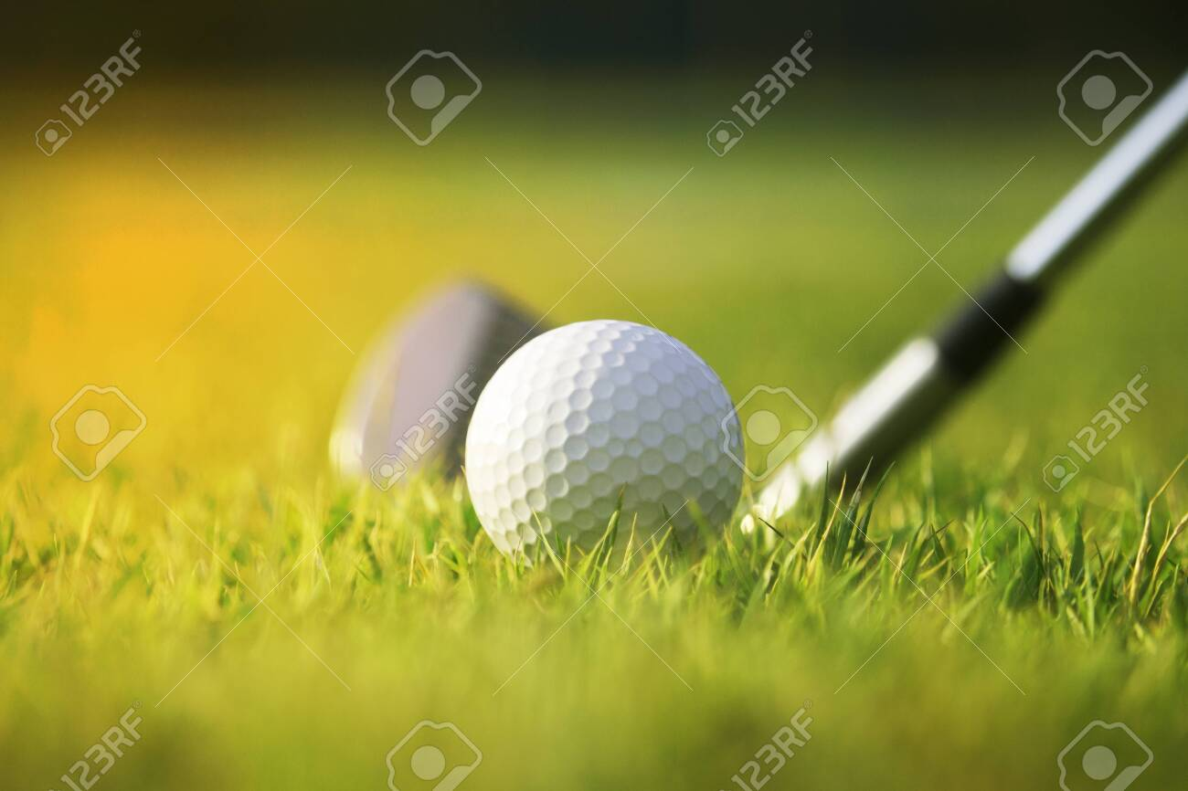Golf clubs and golf balls on a green lawn in a beautiful golf course with morning sunshine.Ready for golf in the first short.Sports that people around the world play during the holidays for health. - 141377067