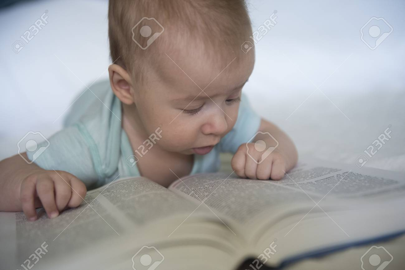 Portrait Of Cute Baby Girl Lying Over And Trying To Read A Big