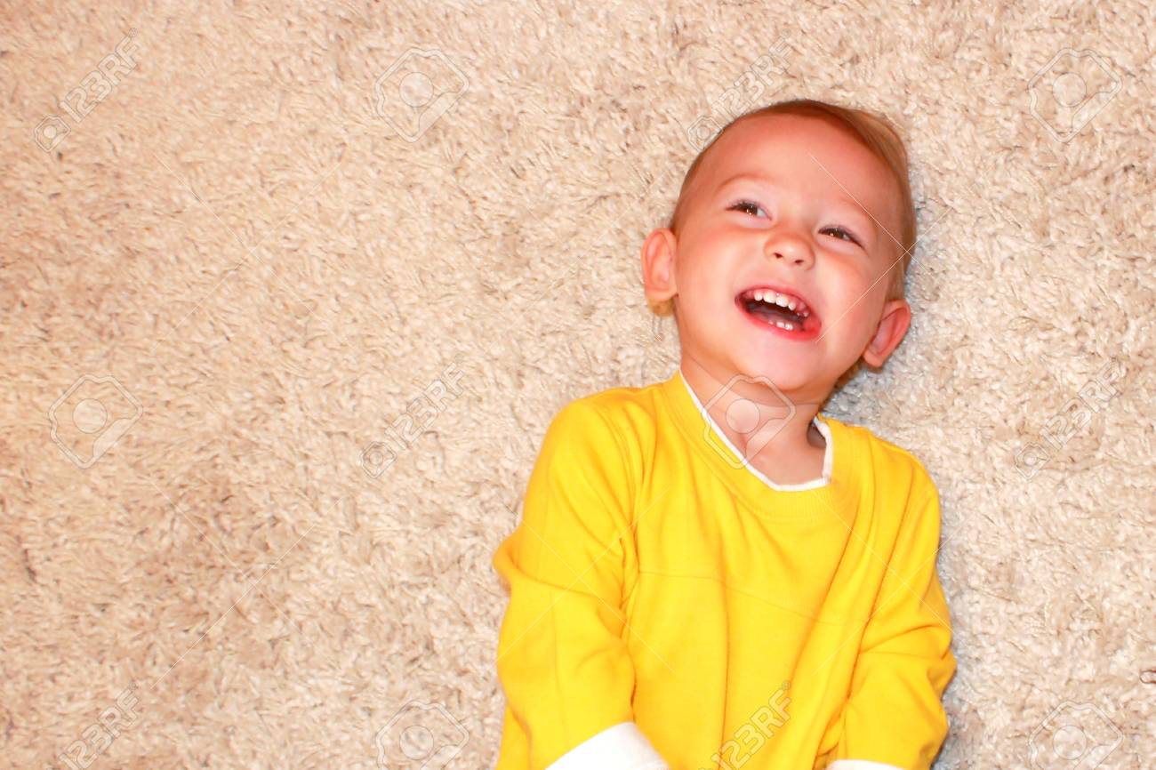 Portrait of a laughing baby lying on a carpet. Stock Photo - 11471606