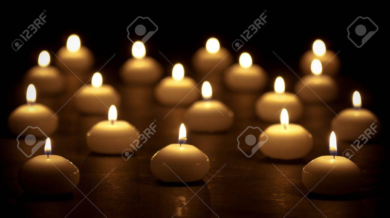 Group of burning candles at a black background with selective focus - 11156597