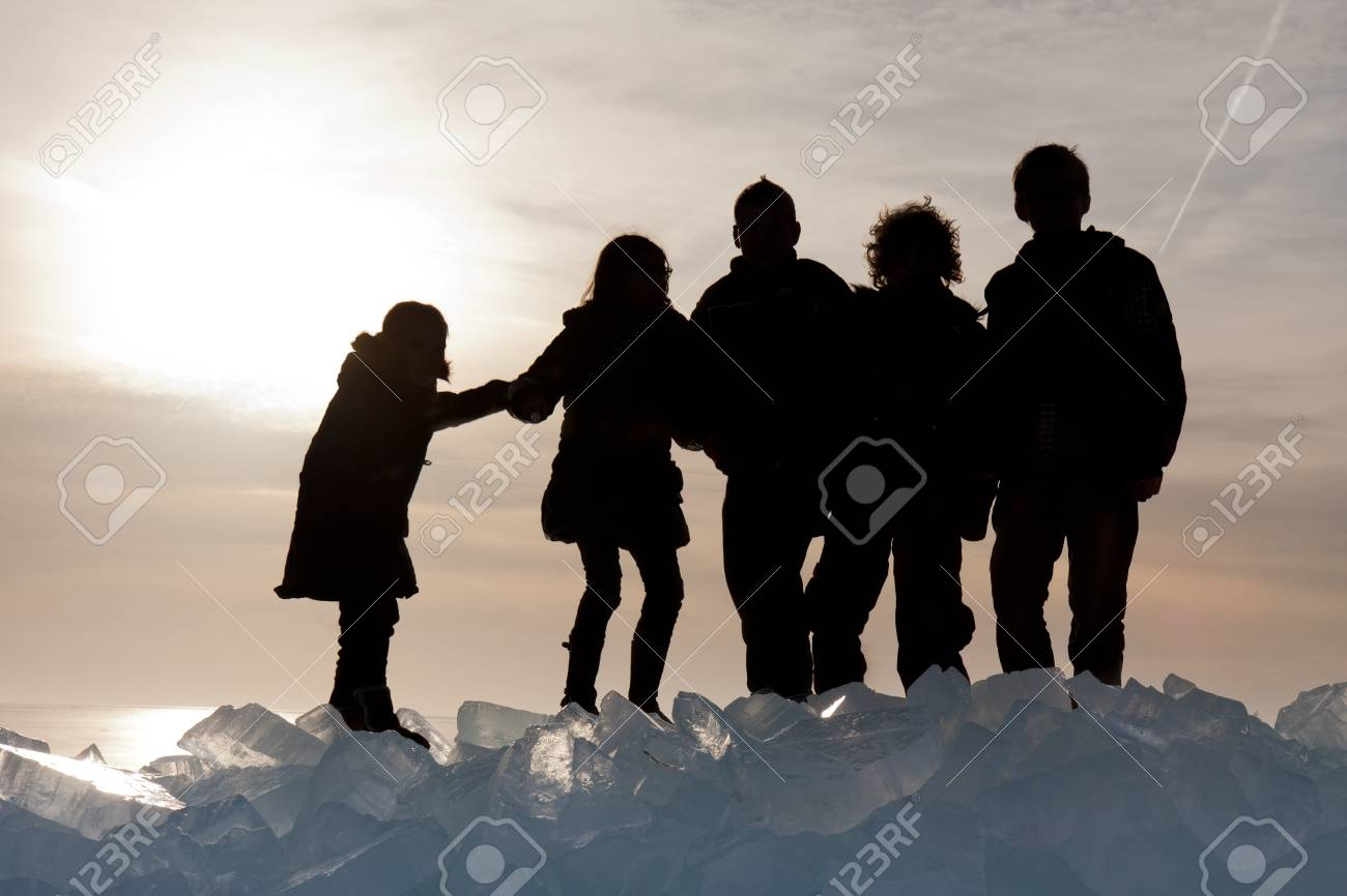 Silhouette of children on Ice hummocks at sunset in the Netherlands Stock Photo - 12623091