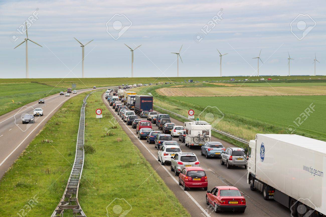 LELYSTAD - AUGUST 17: Traffic moves slowly along a busy highway along a dike and wind turbines on August 17, 2012 in Lelystad, The Netherlands - 17393180