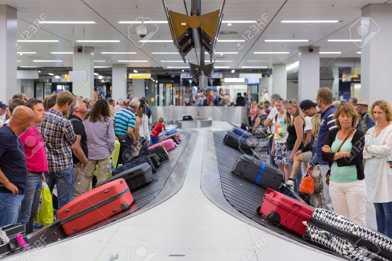 AMSTERDAM, THE NETHERLANDS - AUG 14: Airplane travelers are waiting for their luggage from a conveyor belt at Schiphol airport on August 14, 2014 in Amsterdam, The Netherlands - 30847063