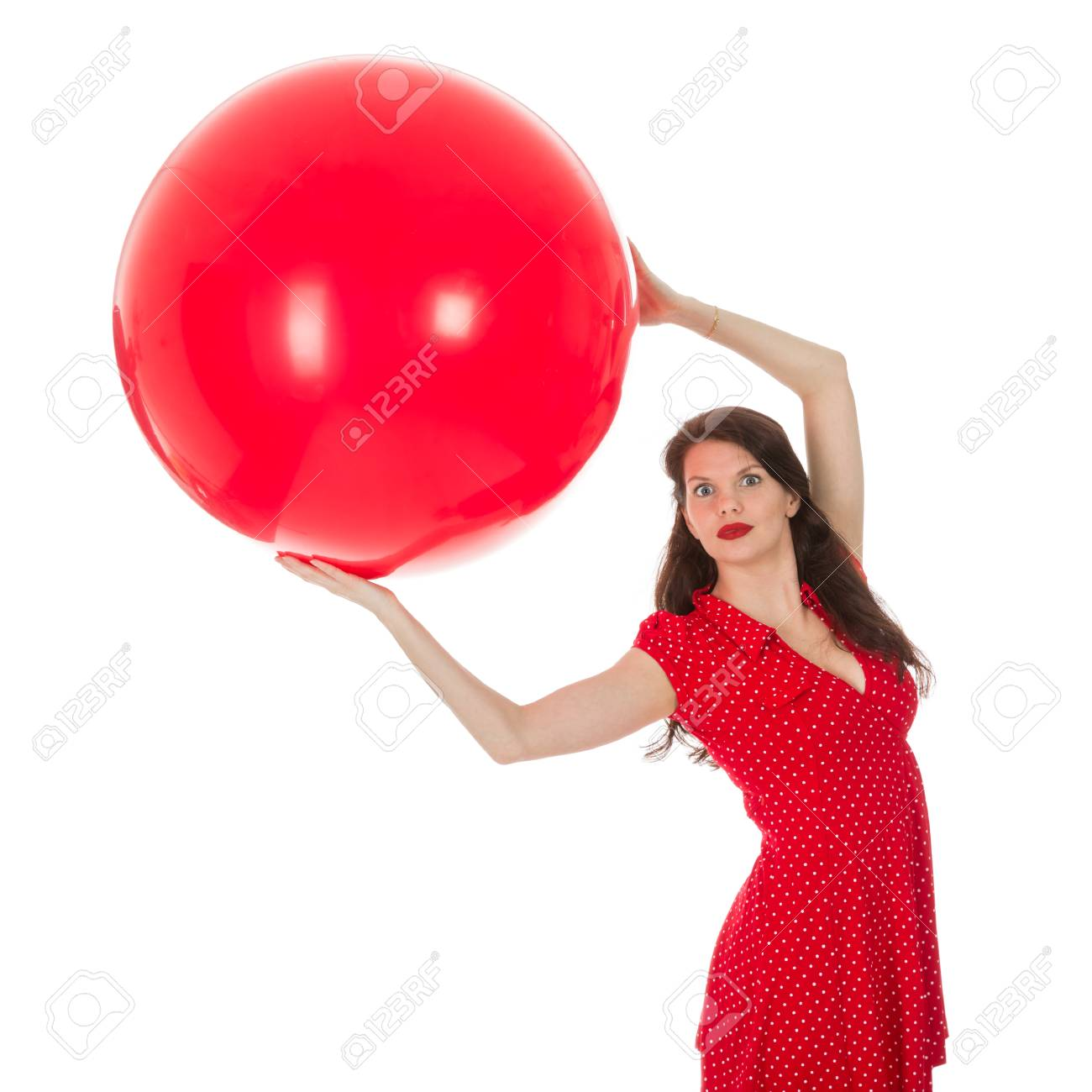 95e8dc33a Beautiful woman in red dress holding a big red balloon above her head  isolated on a