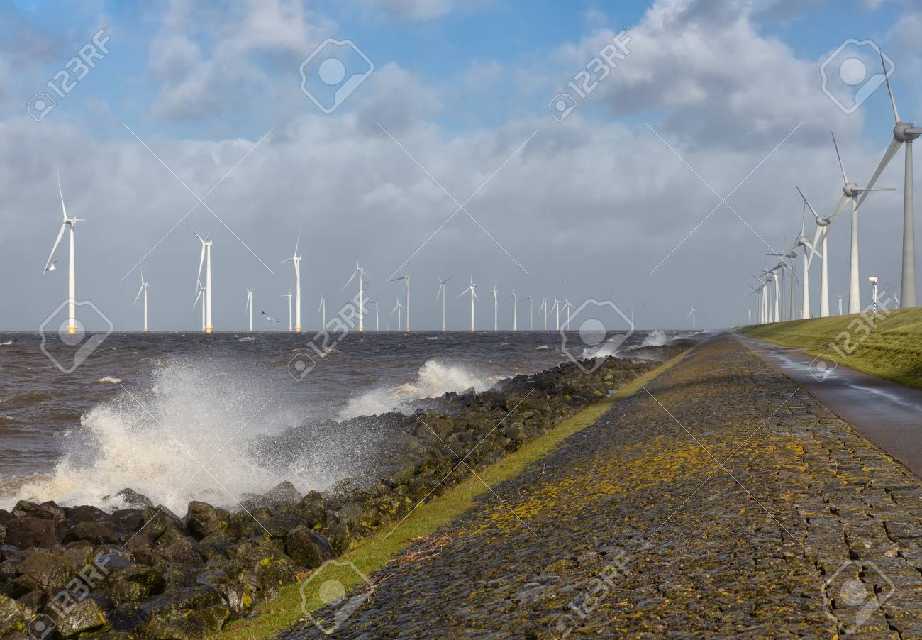Dutch sea with off shore wind turbines and breaking waves at the shore - 118514252