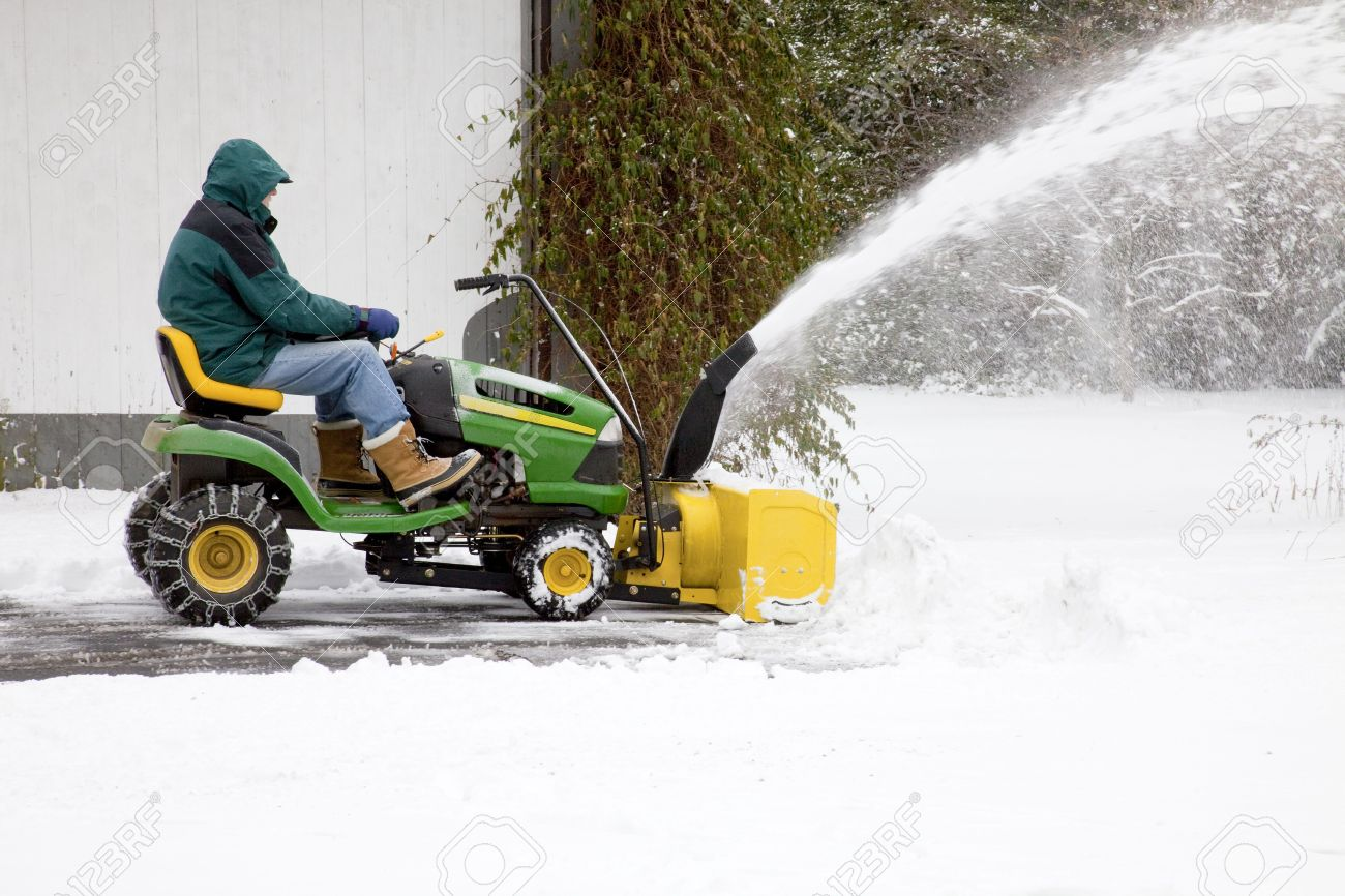 Side View Of Middle Aged Man On Riding Snow Blower Clearing Stock