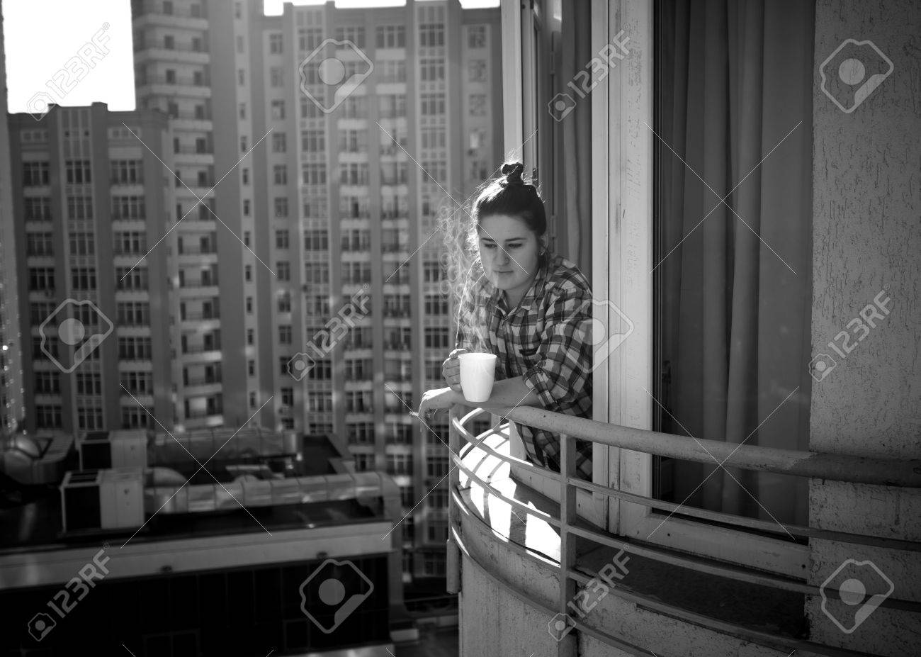 Black and white photo of depressed woman drinking coffee and smoking cigarette on balcony stock photo