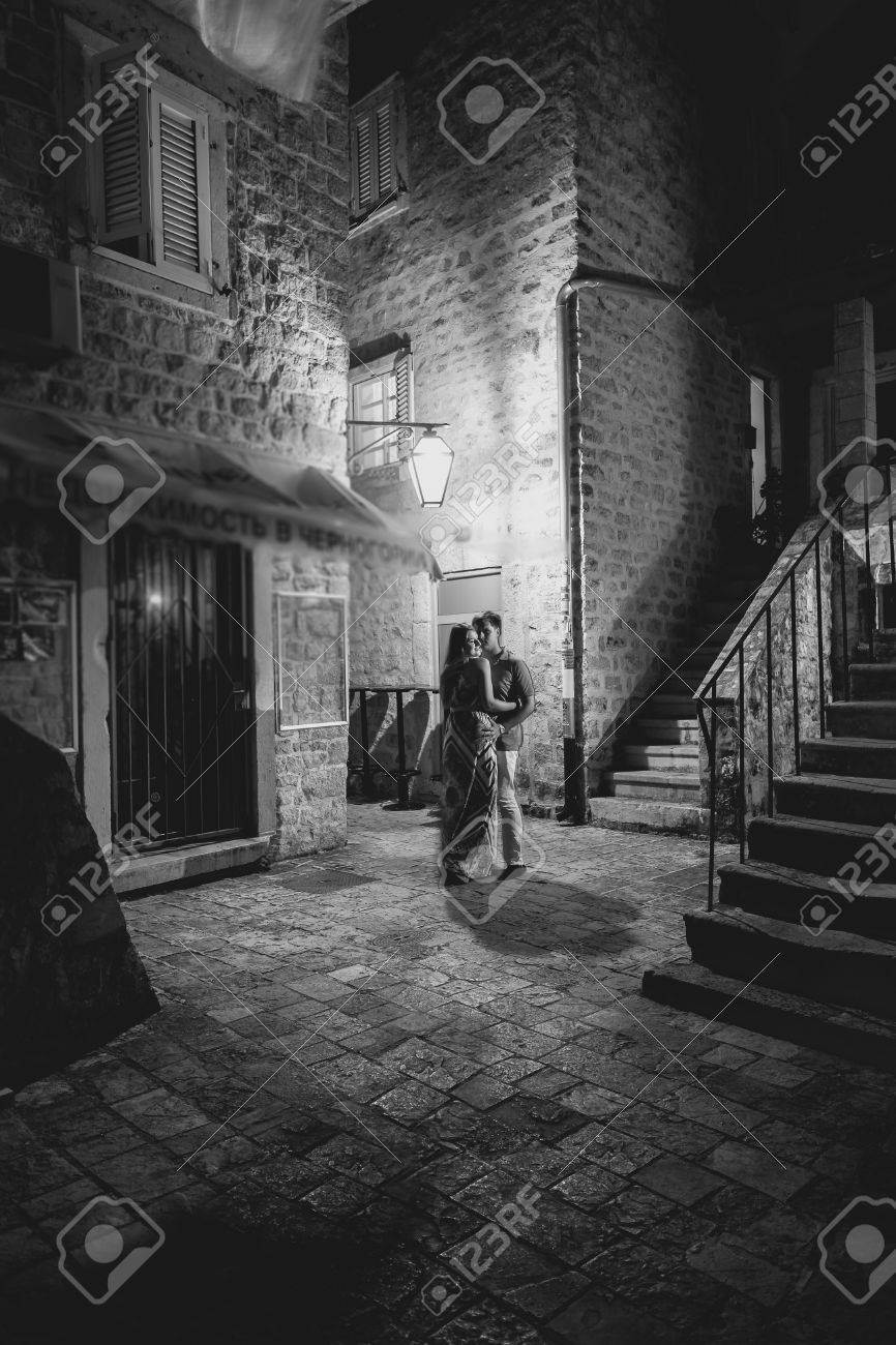 Black and white shot of beautiful romantic couple kissing at night on street of old city