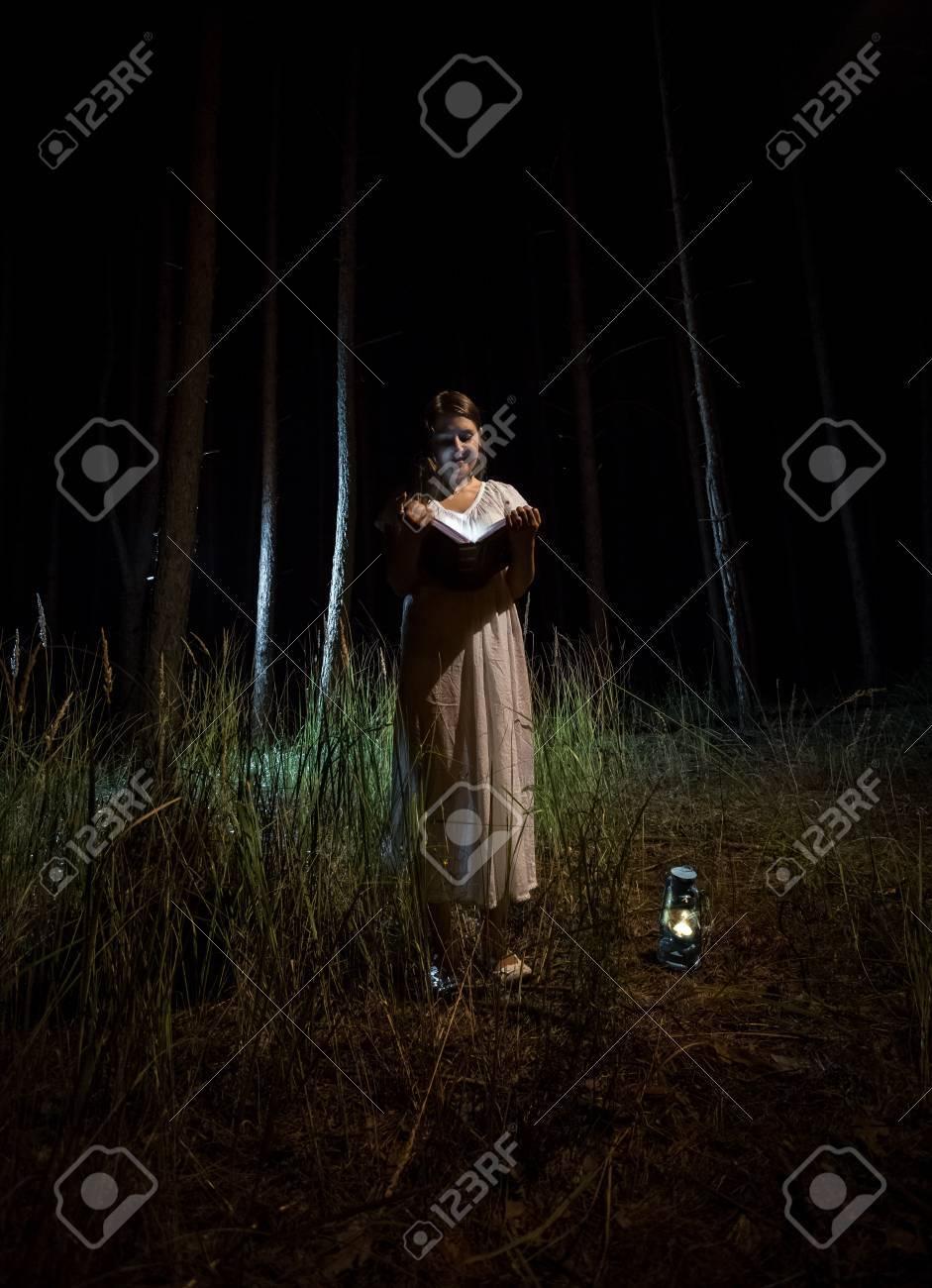 6fbae15ff Foto de archivo - Mujer joven en libro de lectura camisón en el bosque de  noche