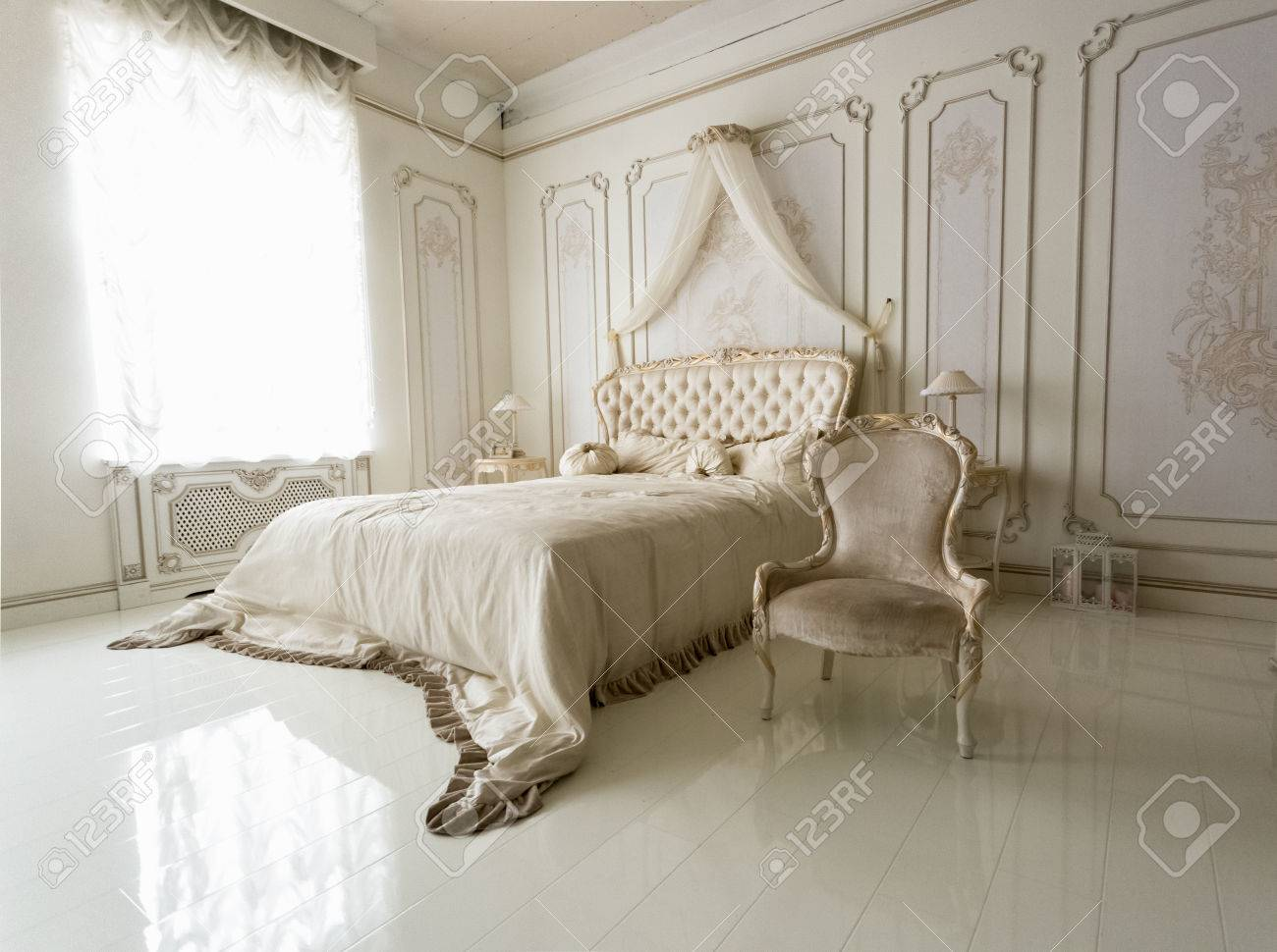 Beautiful interior of classic white bedroom with big bed and..