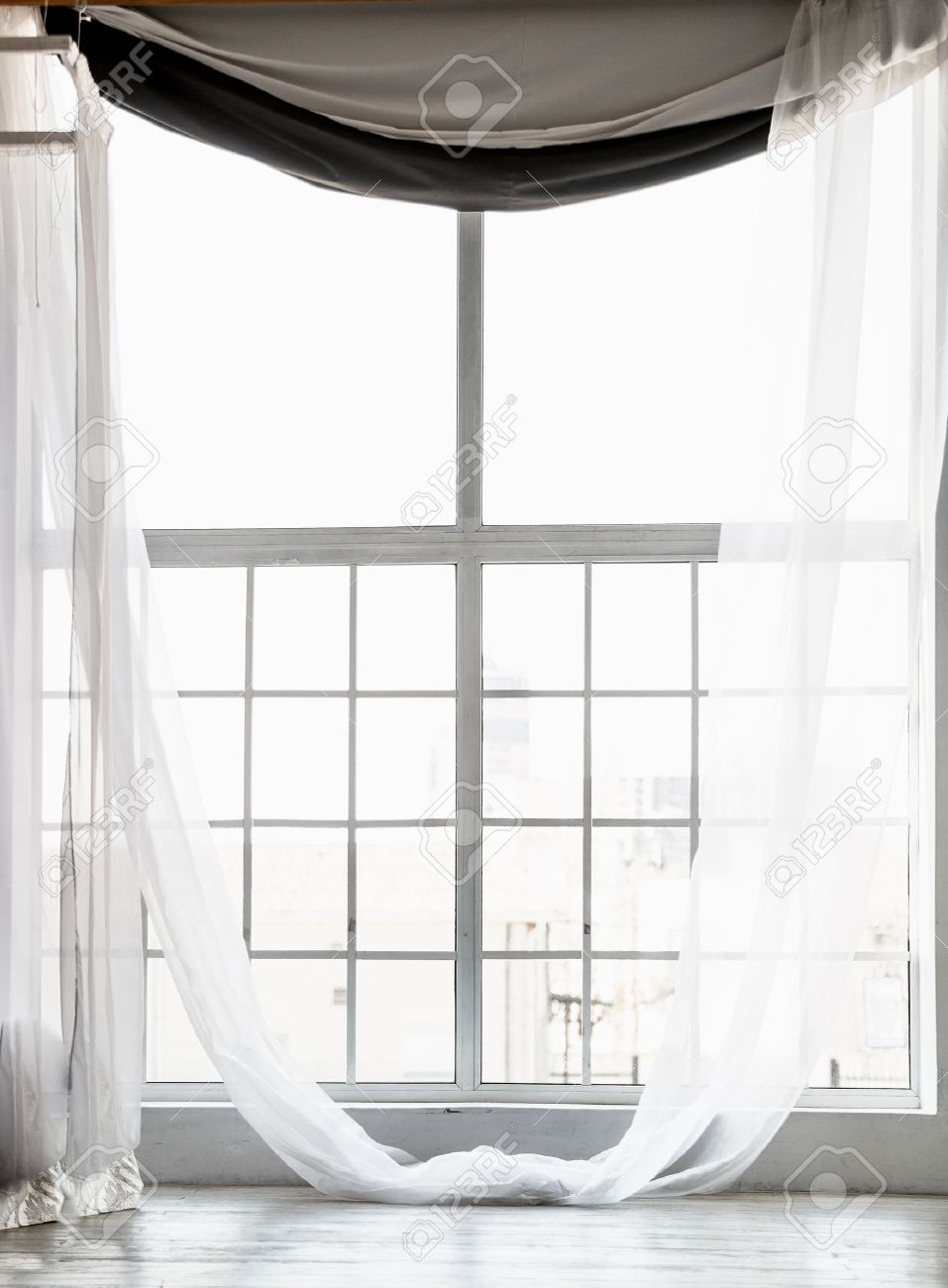 Beautiful high window from ceiling to floor with long white curtains stock photo 38622614