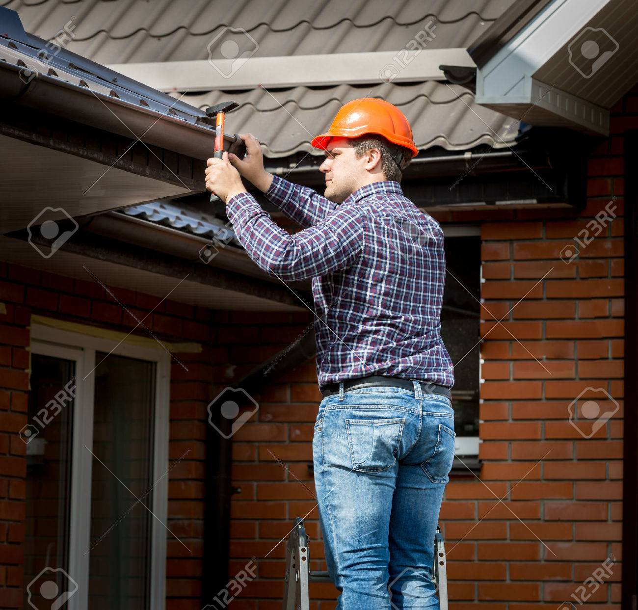 Professional carpenter hammering roof boards with hammer - 41600633