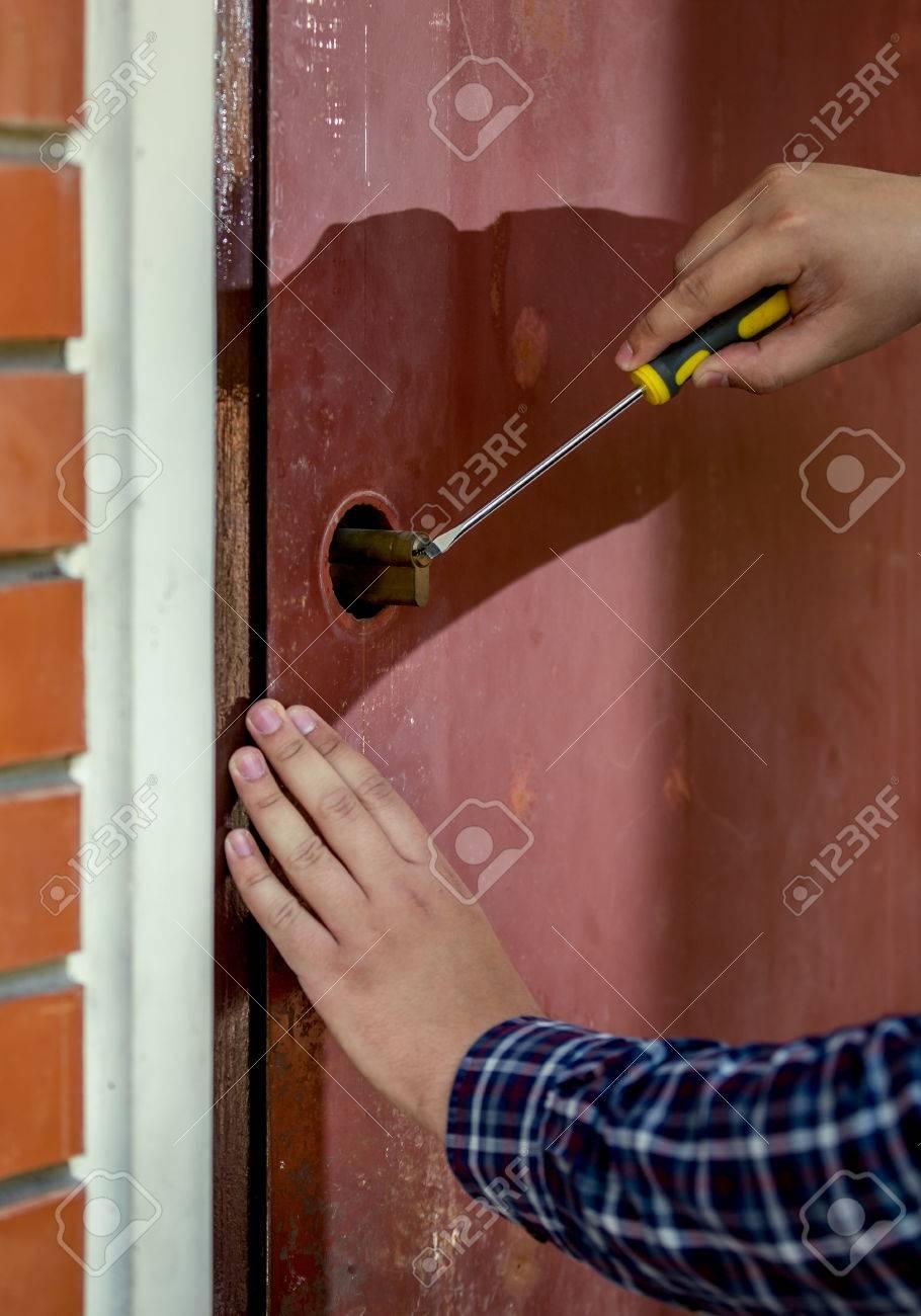 Closeup Shot Of Carpenter Trying To Open Door Lock Using Screwdriver