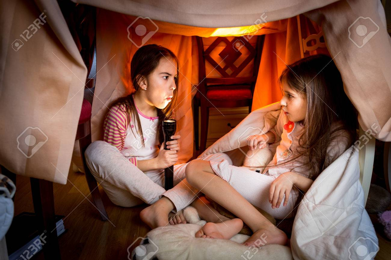 Portrait of elder sister telling scary story to younger one at late night in bedroom - 41163815